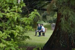 two people sitting on a bench among trees