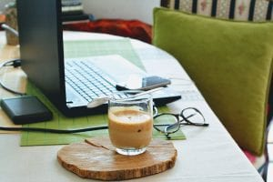 laptop, coffee cup, and glasses on table